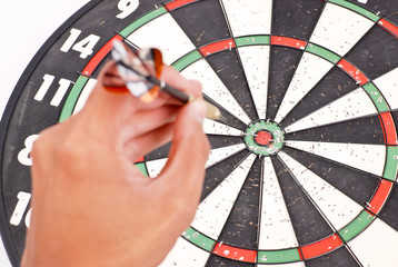 Bulls Eye Focused with Hand About to Throw a Dart in Foreground