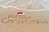 Fototapety Merry Christmas written on tropical beach sand