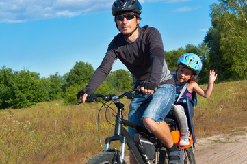 Family cycling. Father with kid riding bicycle outdoors