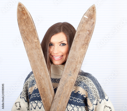 young woman in sweater holding old wooden ski