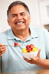 Senior man eating fruit