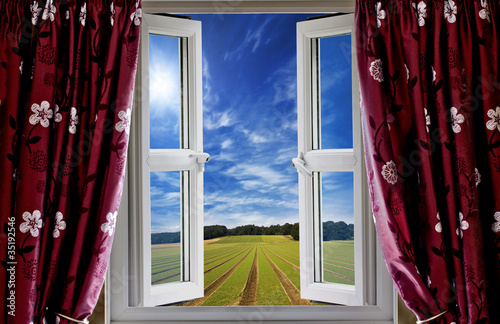 Window view onto arable farmland and blue skies