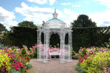 White wrought iron arbour in an English garden