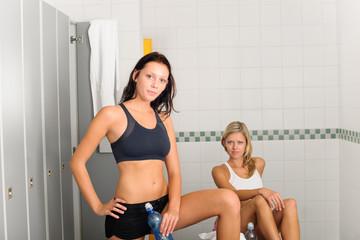 Locker room two sportive women getting ready