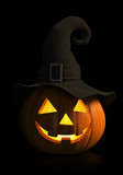 Halloween - carved pumpkin with witch hat glowing in the dark