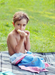Boy eating a sandwich at a picnic.