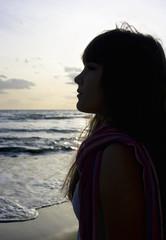 Joven al atardecer en la playa.
