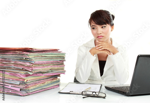 young business woman with laptop and many paper