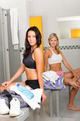 Locker room two sportive women sitting fitness
