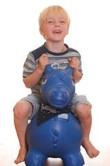 Kleiner Junge reitet Spielzeugpferd