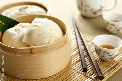 Dimsum in a bamboo basket by tea pot and cups