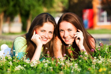 Two girlfriends in park with a mobile phones
