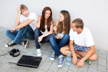 small group of students sitting on street