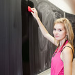 pretty young college student erasing the chalkboard