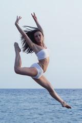 ragazza bionda che salta sull'acqua del mare vestita bianco