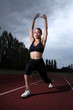 Athlete woman lunge stretch on athletics track