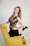 pretty woman smiling with pleasure  and kneeling in a chair poster