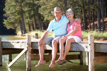Senior couple sitting by lake