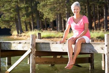 Senior woman sitting by lake