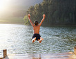canvas print picture - Young boy jumping into lake