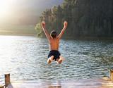 Fototapety Young boy jumping into lake
