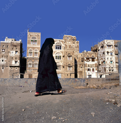 A veiled Muslim woman walks on a Sana a street, Yemen