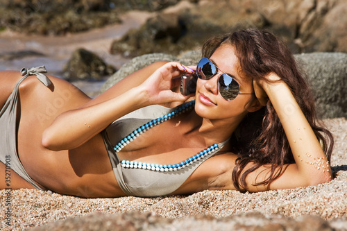 Beautiful girl talking on cell phone on a beach.