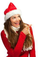 Beautiful woman in santahat pointing at copyspace
