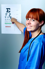 female oculist doctor examining patient with an eye chart behind
