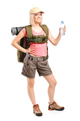Woman hiker with backpack holding a bottle of water