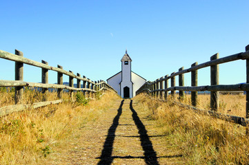 Small wooden church in the prairies during autumn