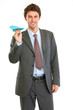 Smiling modern businessman with paper airplane
