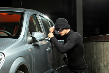 Thief with a robbery mask trying to steal an autobmobile