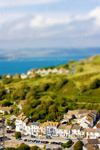 Fake toy village view over rolling hills and sea