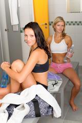 Locker room two sportive women sitting smiling