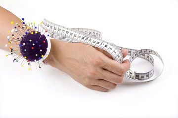 Hand with pincushion and measuring tape