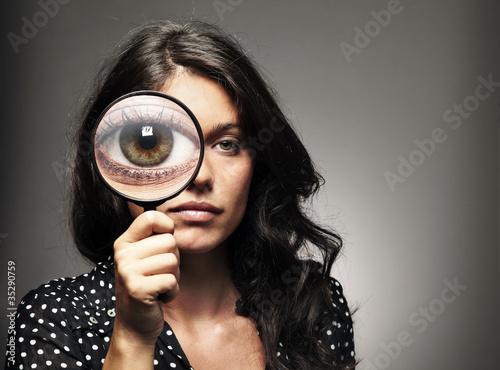 Retrato de chica observando, buscando con una lupa