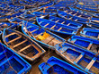 Blue fishing boats tied together in harbor - 35292993
