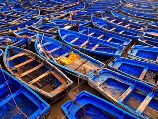 Blue fishing boats tied together in harbor
