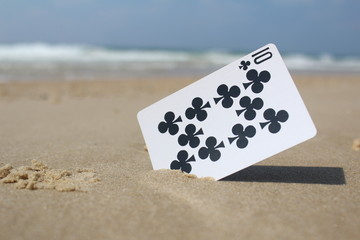 Playing card - the card 10 club, in the sand, beach background