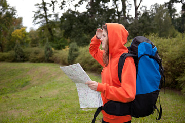 young woman with map, rucksack outdoors in windy day