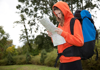 young woman with map, rucksack on her back outdoors