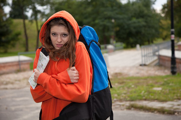 young woman with map rucksack on her back outdoors