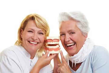 Zahnarzt und Seniorin mit Gebiss