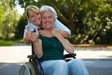 Frau im Rollstuhl zeigt Daumen hoch