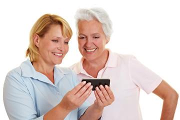 Seniorin schaut auf Smartphone