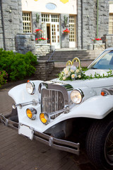 White vintage wedding car decorated with flowers