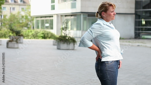 Woman in city with back pain