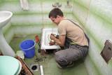 Fototapety Plumber cleaning  drain in bathroom