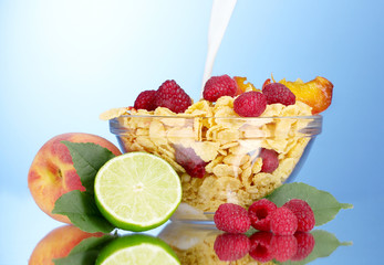 tasty cornflakes, fruit and milk in glass bowl